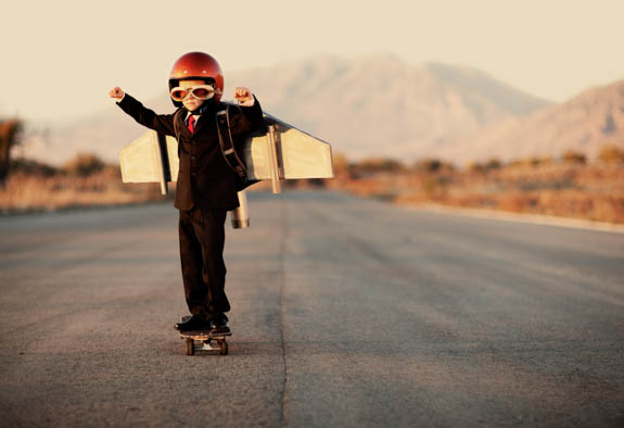child with wooden wings on skateboard