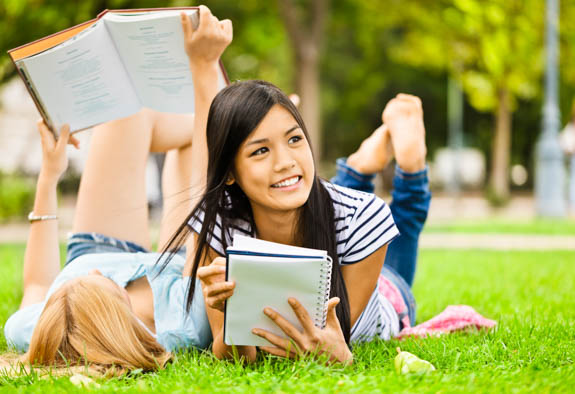 Girls on grass with books